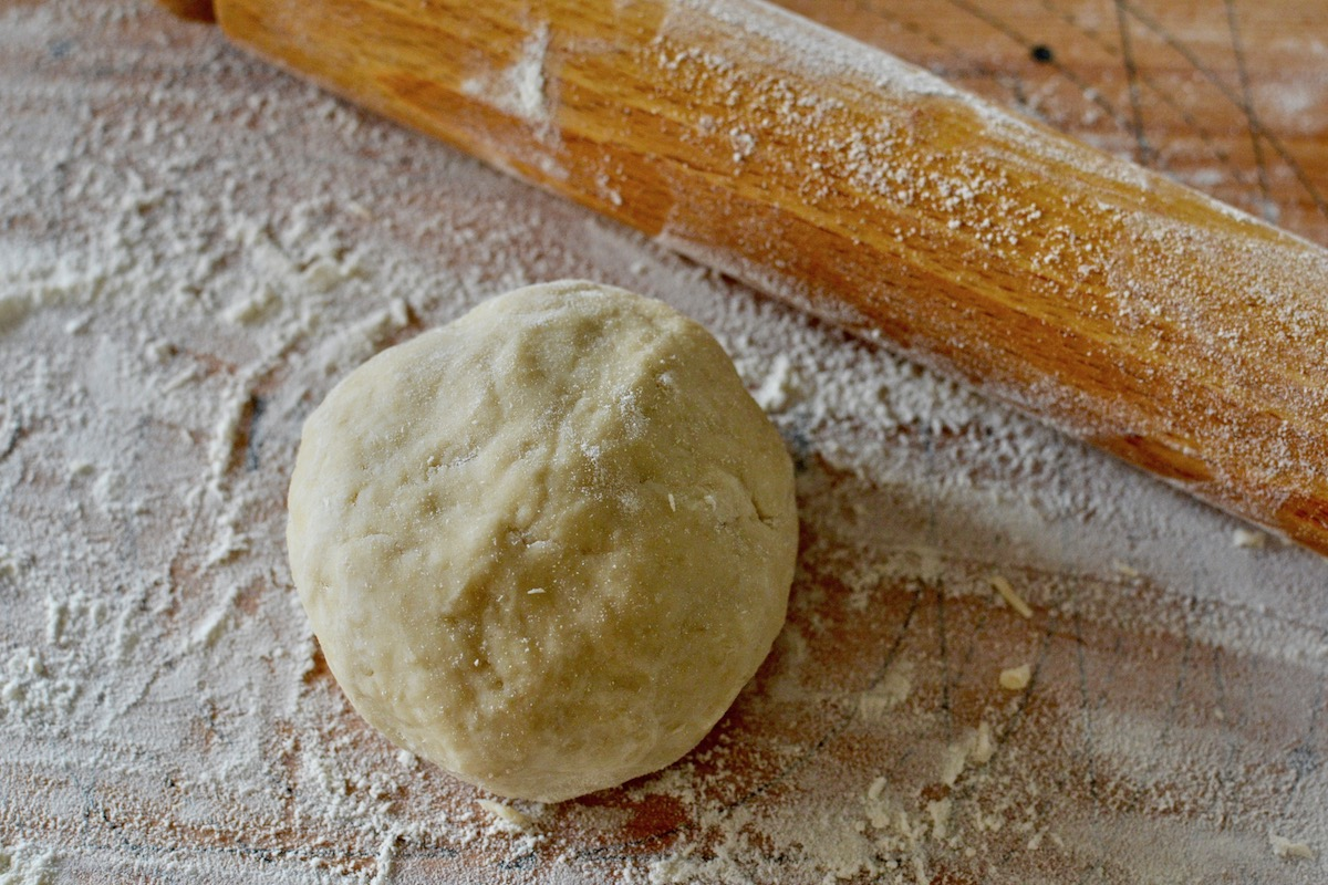 A ball of vegan pastry on a floured board, ready to roll out