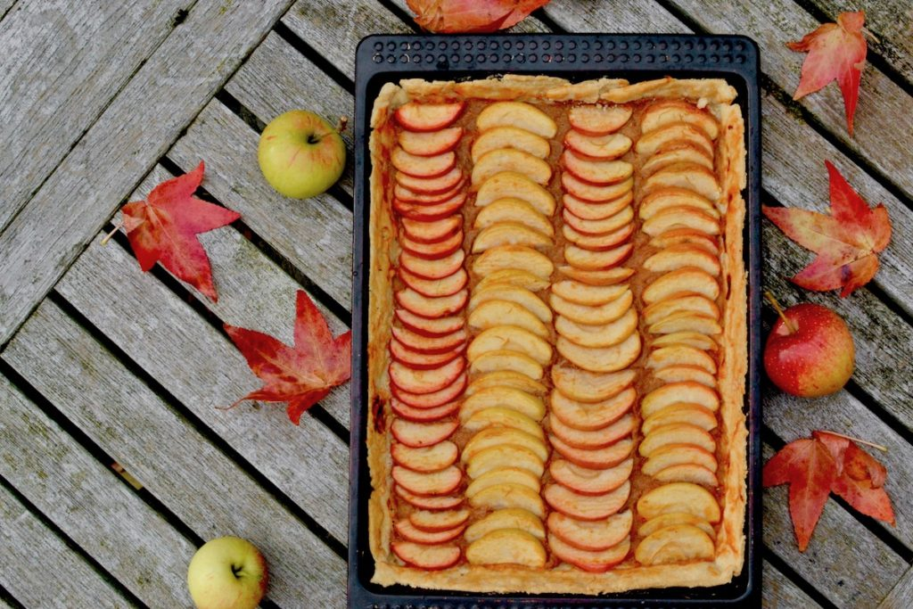 Vegan apple tart with autumn leaves and windfall apples