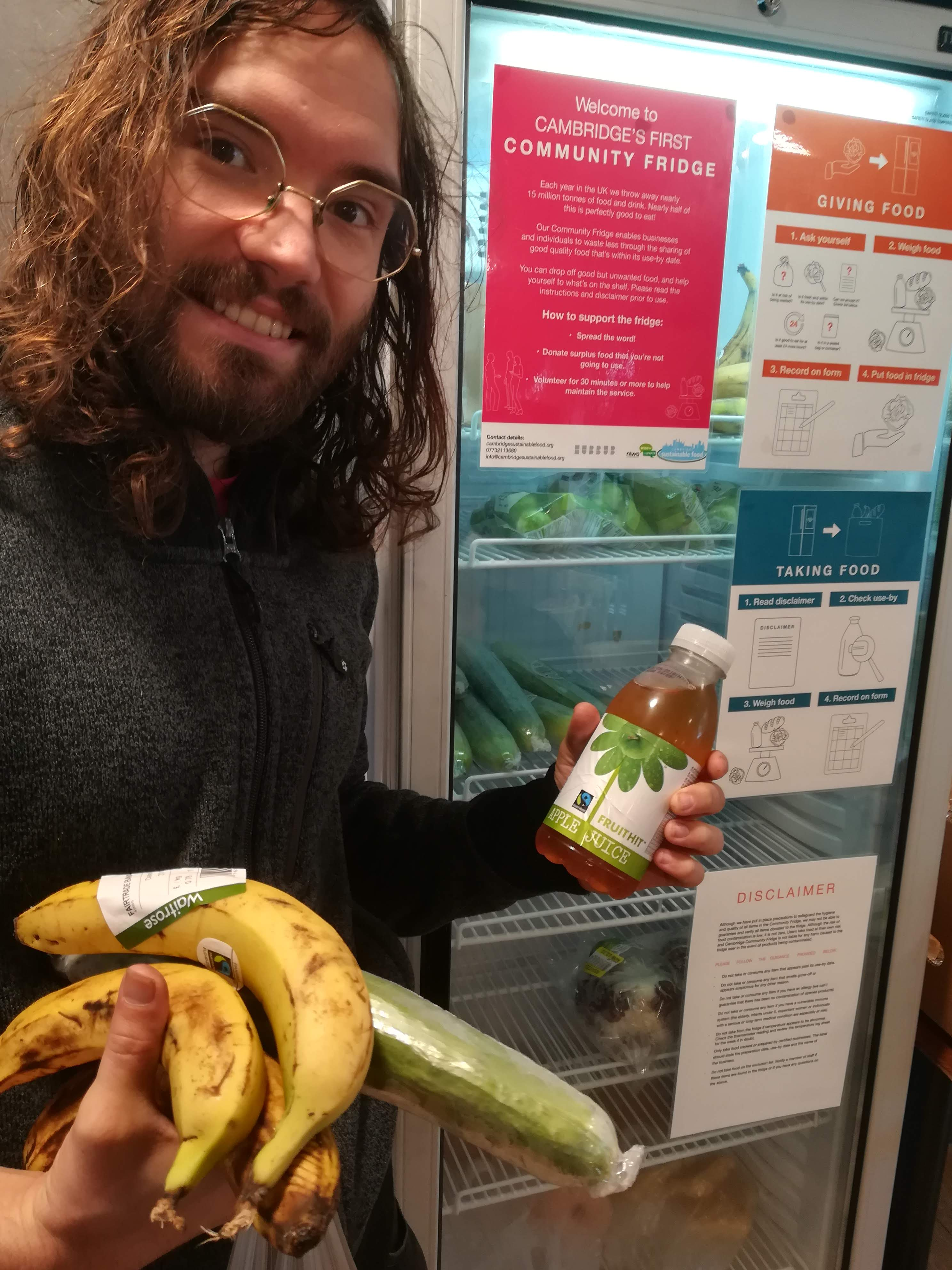 Paul holding bananas, a cucumber and some apple juice from the community fridge