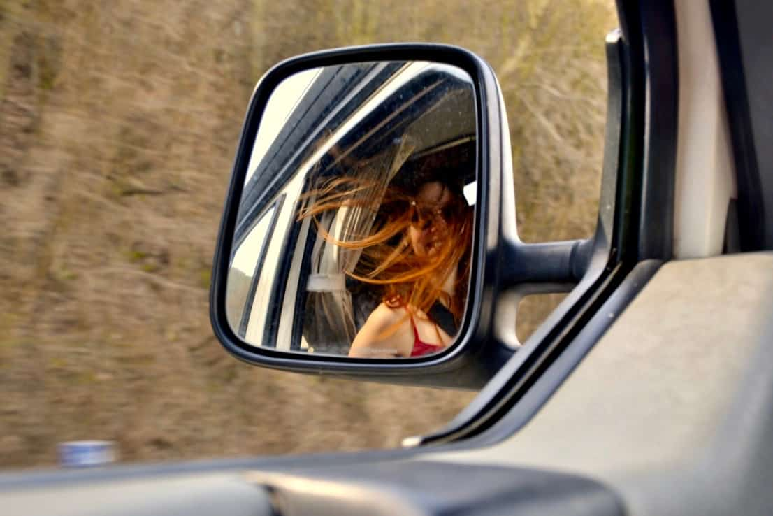 A reflection of a smiling Sophie in a wing mirror