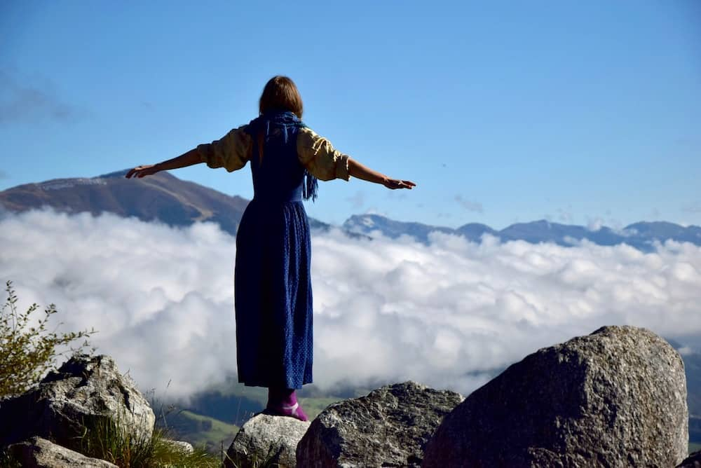 Sophie stands with her arms spread above a cloud filled valley