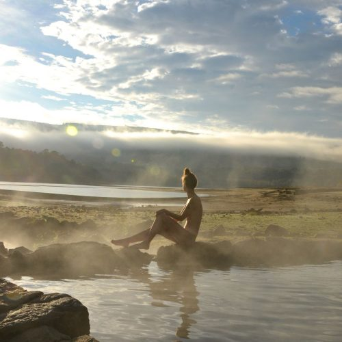 A bather enjoys the sunrise at the thermal springs
