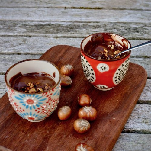 Pots of chocolate dessert with hazelnuts