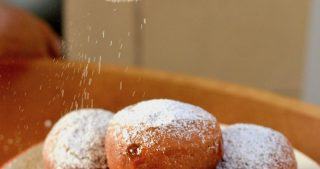 Dusting the doughnuts with icing sugar