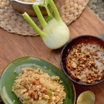 A delicious plate full of vegan fennel risotto and a brass spoon