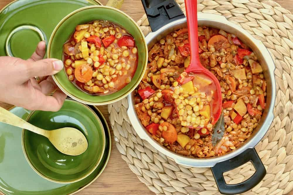 Serving vegan lentil stew with a red ladle