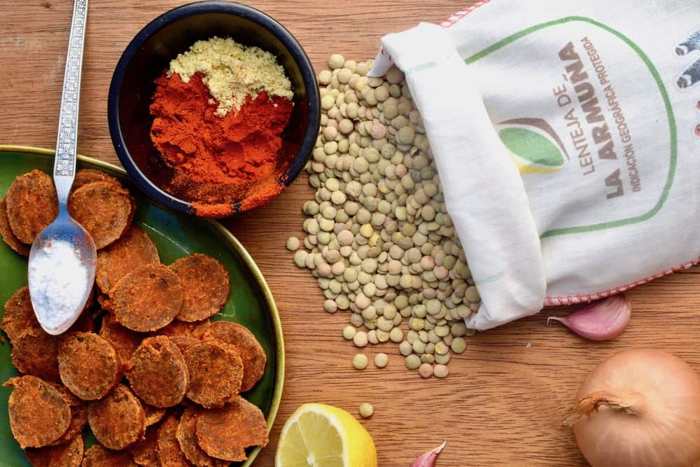 A bag of lentejas de la armuna, spices and vegan chorizo on a plate