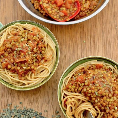 Two bowls of spghettis topped with lentil ragu next to uncooked green lentils on a board.