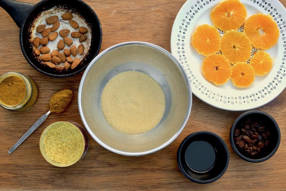 Ingredients for a couscous salad - couscous, oranges, almonds, raisins, spices, and oil