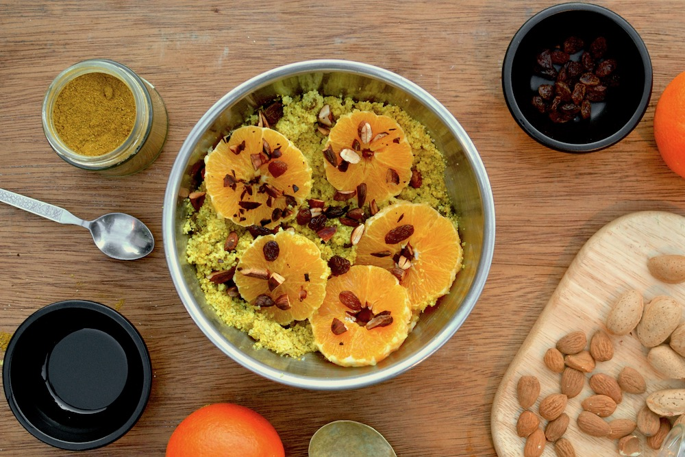A bright couscous salad with orange slices on top