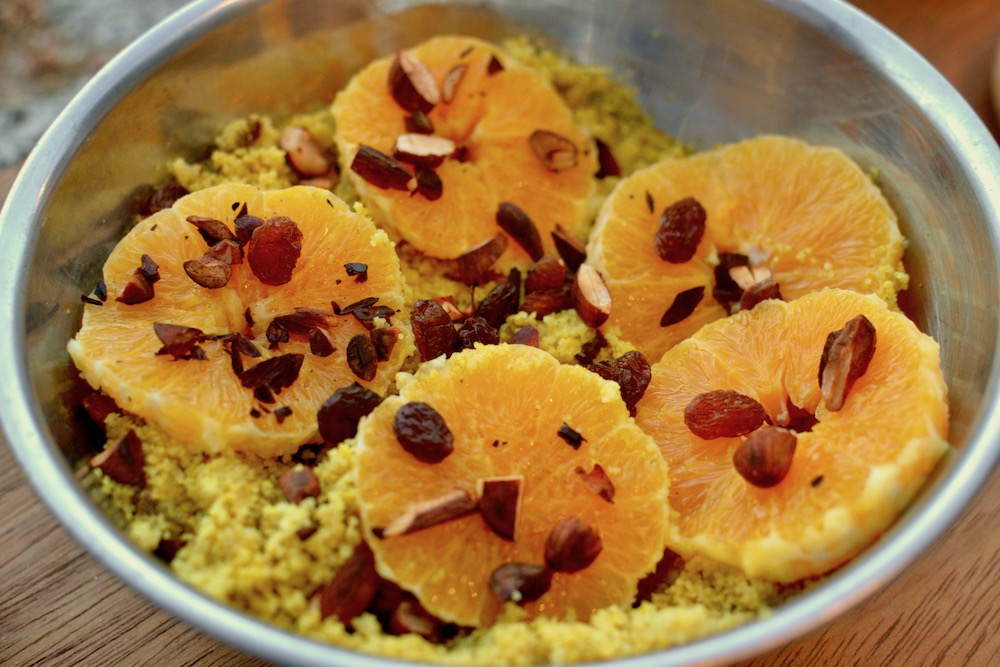 Oranges, almonds and raisins scatter on top of a couscous salad