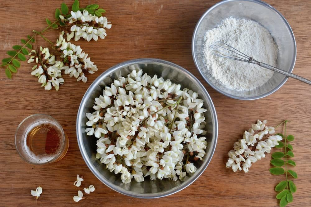 A bowl full of acacia flowers, next to a glass of beer and a bowl of flour