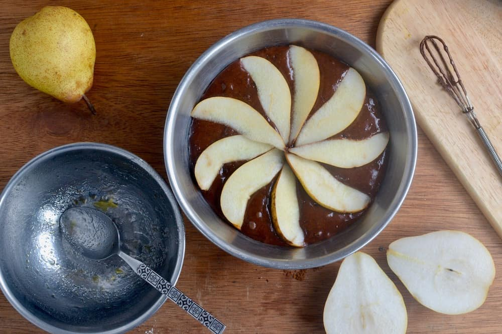 Covering the vegan chocolate cake batter in pears