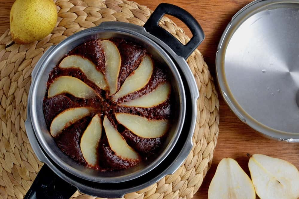 A vegan chocolate cake with pears inside a pressure cooker