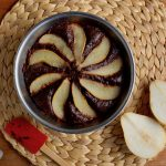 A metal bowl containing chocolate cake decorated with sliced pears