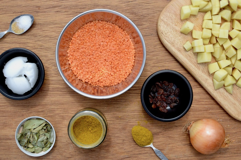 Ingredients ready to make a vegan dal - red lentils, potatoes, raisins, coconut oil, onion and spices