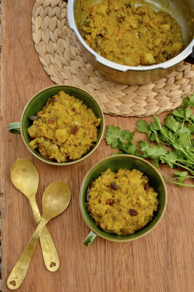 Two bowls of red lentil dal waiting to be topped with coriander