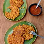 Crispy, yellow corn fritters on two green plates