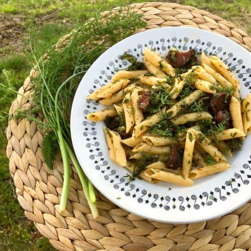 A plate of penne pasta wiht chunks of vegan chorizo and wild fennel