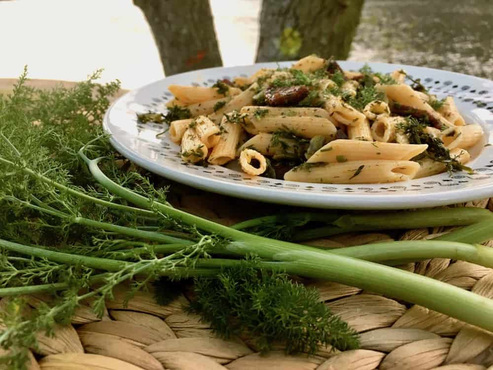 The green stems of wild fennel in front of a vegan fennel pasta dish