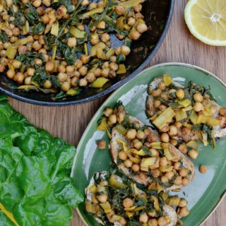 A pan with stirfried chickpeas and chard, next to a plate with three slices of toast