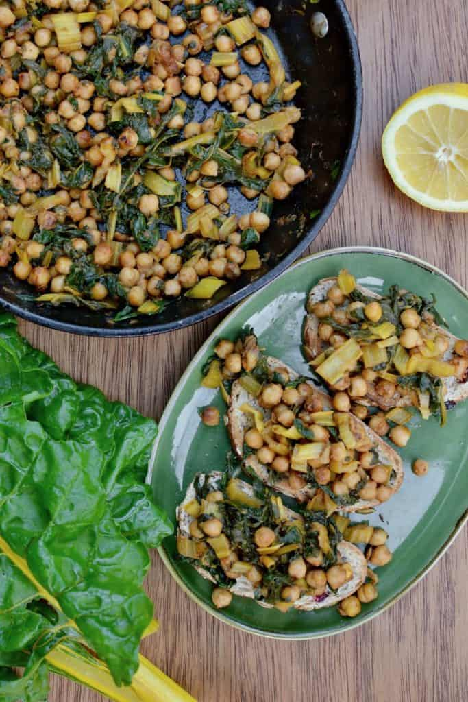 A pan full of fried chickpeas and greens, alongside three chickpea toasts