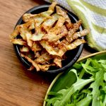 A small dish of crispy, golden brown crisps next to a plate of rocket