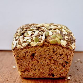 The end of a loaf topped with pumpkin seeds, sunflower seeds and oats