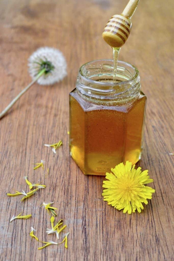 A jar of golden brown runny vegan honey substitute