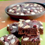 Squares of chocolate brownie topped with cranberries and almonds, in front of a skillet
