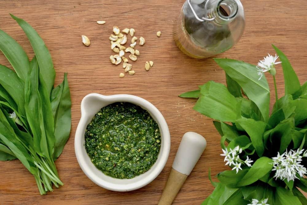 Wild garlic leaves alongside a bowl of wild garlic pesto