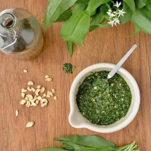 A bowl full of pesto, surrounded by wild garlic leaves, cashews nuts, and a bottle of olive oil