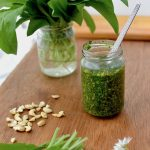 A jar of pesto with a spoon inside, wild garlic leaves and cashews nuts on a board
