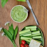A bowl of green hummus decorated with wild garlic flowers, next to a plate of crudites and crackers