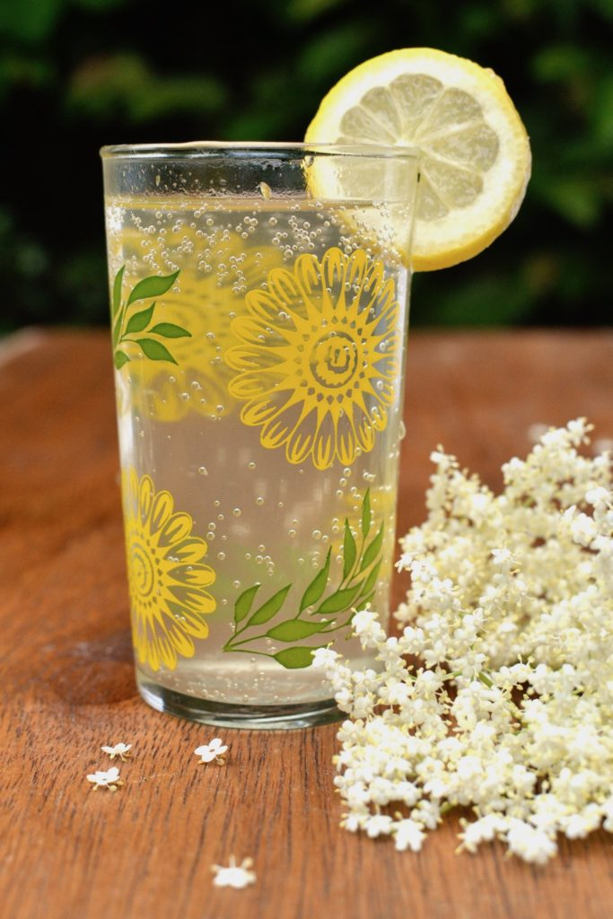 A glass of homemade elderflower cordial with sparkling water