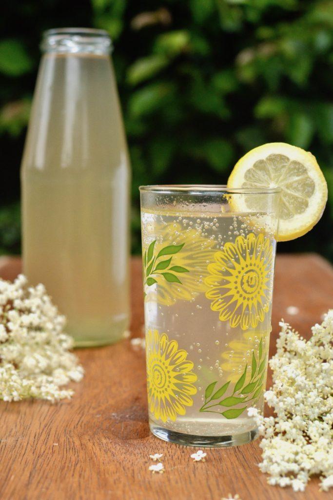 A bottle of elderflower cordial behind a glass of sparkling elderflower drink in a patterned glass