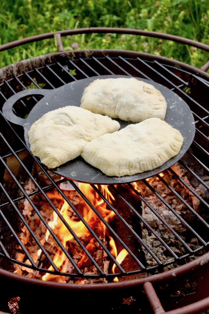 Three dessert calzone cook on a cast iron skillet over a campfire