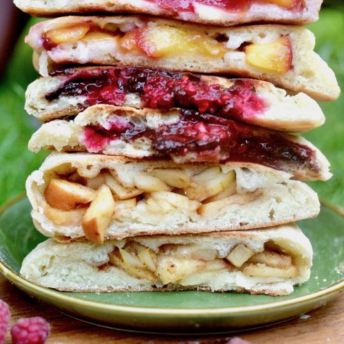 A stack of calzone cut in half to reveal their fruity fillings