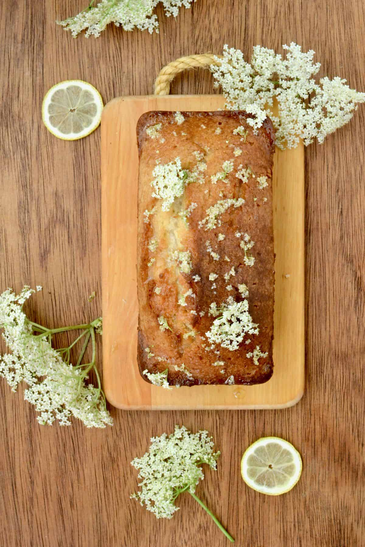 A vegan loaf cake on a wooden board surrounded by fresh elderflowers