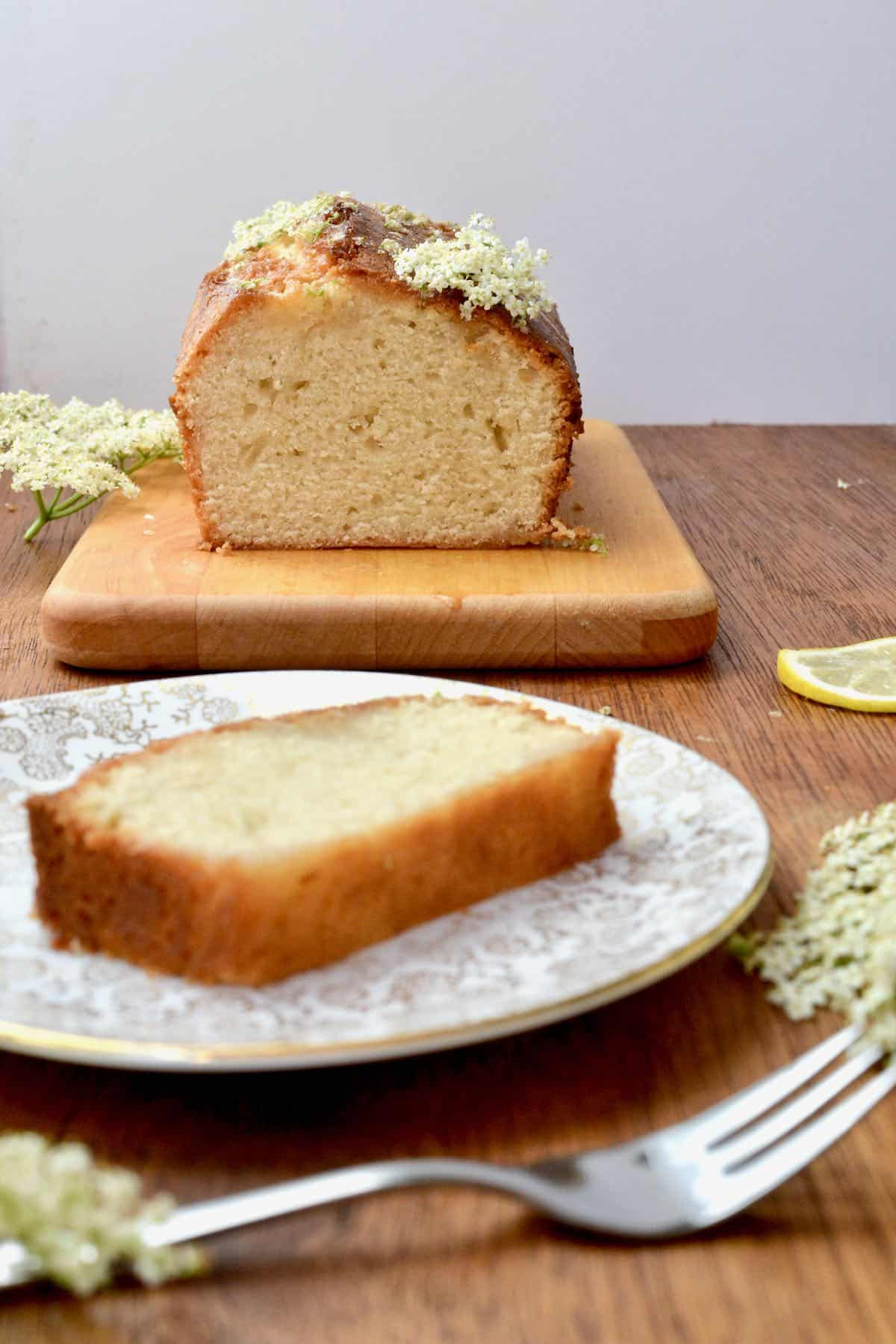A slice of elderflower cake on a plate, with the loaf in the background