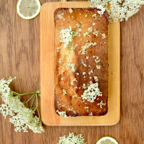 A golden brown loaf cake decorated with elderflowers