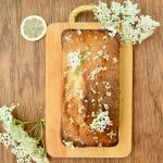 A vegan loaf cake on a wooden board, decorated with elderflowers