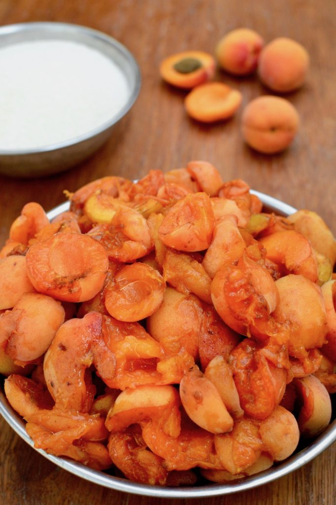 A bowl of soft, super-ripe bruised apricot halves, which are perfect for making jam.