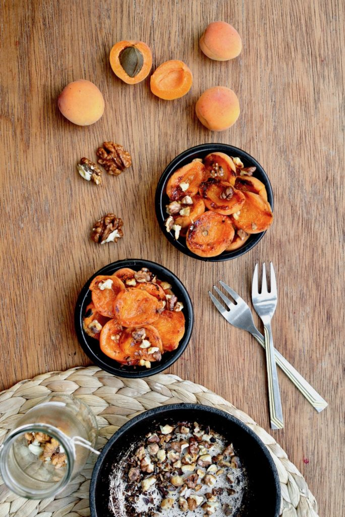 Grilled apricot and walnut dessert surrounded by fresh apricots and a jar of walnuts
