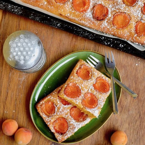 Two square pieces of vegan apricot cake, surrounded by extra fruit, a sugar sifter and the remaining cake
