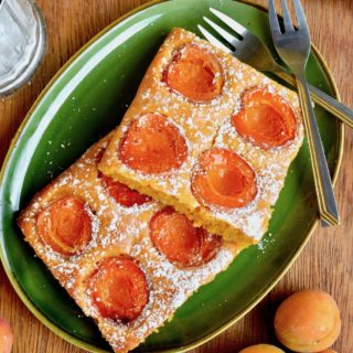 Two servings of apricot cake, sprinkled with icing sugar, on a plate with two forks.