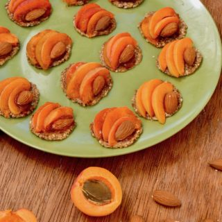 A green plate coverd in mimi apricot and almond topped no bake tarts