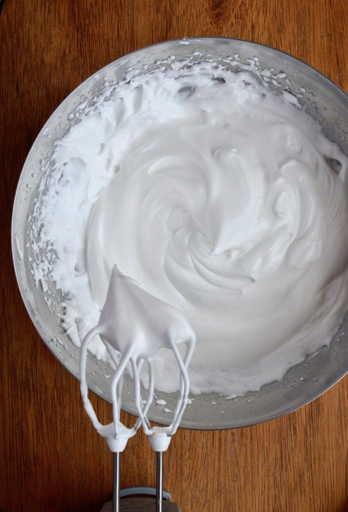 Aquafaba meringue holding stiff peaks from the beathers of an electric whisk