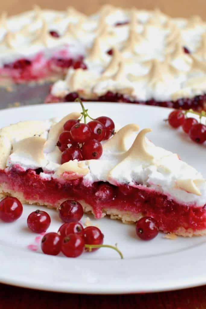 A piece of red currant meringue tart on a plate with fresh redcurrant garnish