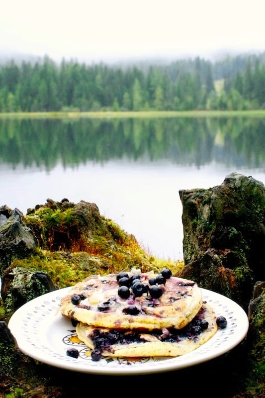 A plate of wild blueberry pancakes in front of an alpine lake